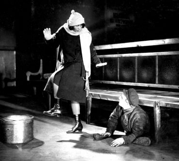 girl-with-the-hat-box-1927-002-girl-in-mid-step-over-man-under-bench